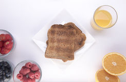 Wholemeal toast surrounded by fruit Stock Images