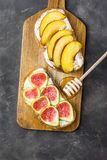 Wholemeal Toasts with Cream Cheese Fresh Ripe Figs and Peaches on Wood Cutting Board. Drizzled with Honey. Dark Stone Background. Flat Lay Royalty Free Stock Image