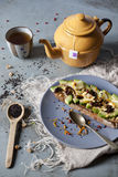 Wholemeal vegan toast with avocado slices and black sesame seeds on table with teapot Royalty Free Stock Images
