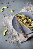 Wholemeal vegan toast with avocado slices, lemon, orange peel, pink pepper and seeds on plate Royalty Free Stock Photo