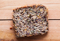 Wholemeal, wholewheat slice of bread on wooden table. Organic, healthy food Stock Images