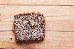 Wholemeal, wholewheat slice of bread on wooden table. Organic, healthy food Royalty Free Stock Photo