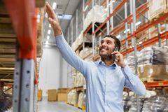 Businessman calling on smartphone at warehouse. Wholesale, logistic business and people concept - smiling businessman calling on smartphone at warehouse Royalty Free Stock Photography