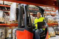 Loader with clipboard in forklift at warehouse. Wholesale, logistic, shipment and people concept - loader with clipboard in forklift loading boxes at warehouse Stock Image