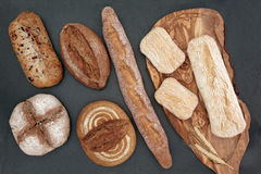 Wholesome Bread. Homemade bread selection on olive wood board on slate background Stock Images