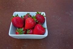 Wholesome Strawberries in a white bowl on a brown textured backg stock image