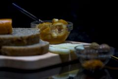 Wholewheat breads with cheese, jams and green olives on a wooden chopping board with their reflections, close up, macro stock photo