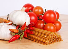 Wholewheat spaghetti with tomatoes and peperoncini. Whole wheat spaghetti with cherry tomatoes, pepperoncini and garlic on a wooden tray Stock Images