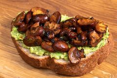 Wholewheat toast on sutting board. Clise up of wholewheat toast with mashed avocado and grilled mushrooms on a cutting board stock photos