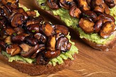 Wholewheat toast on sutting board. Clise up of wholewheat toast with mashed avocado and grilled mushrooms on a cutting board stock photo