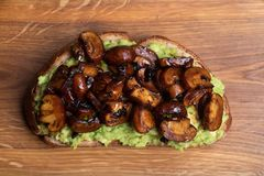 Wholewheat toast on sutting board. Clise up of wholewheat toast with mashed avocado and grilled mushrooms on a cutting board royalty free stock image