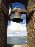For whom the bell tolls solitary bell in stone arch framing sea view. A solitary bell inside a stone archway that frames a view of a turquoise sea and puffy Stock Photo