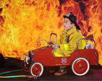 Whoo!  THis is a Hot One!. An adorable preschool fireman looking worried as he drives his vintage fire truck to an inferno Royalty Free Stock Photography
