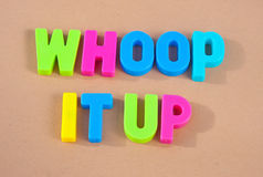 Whoop it up. Text 'whoop it up' in colorful uppercase letters on a beige background, concept of enjoying yourself while you still can Stock Photo