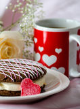 Whoopee pie and heart mug with a rose. Pink and white chocolate is drizzled over a chocolate cake whoopee pie, filled with white cream and decorated with a jelly Royalty Free Stock Image