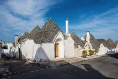 whote trulli房子行在阿尔贝罗贝洛,意大利 免版税图库摄影