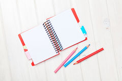 Whtie wooden table blank notepad and colorful pencils Stock Photography