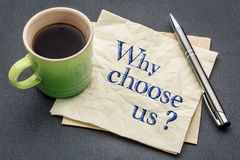 Why choose us?. Handwriting on a napkin with cup of coffee against gray slate stone background Stock Image