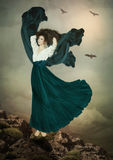 Why do not people fly like birds?. Young girl with long, curly hair, in a dress similar to bird standing on the rock in the clouds, dreaming about flight.Why do Royalty Free Stock Image