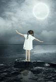Why don't people fly like birds?. The little girl in a nightgown, standing on a rock in the sea under the moonlight simulates the flight of seagulls.Why don't Royalty Free Stock Images