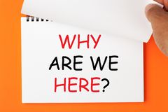 Why Are We Here. `Why are we here?` text on a notebook. Hand turn page. Business concept stock photo