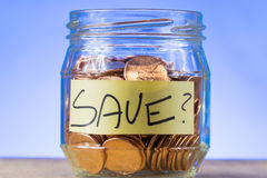 Why Save?. A shot of a small jar of American pennies with the word `Save` inside of it on a piece of paper Royalty Free Stock Photo