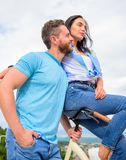 Why women more attracted biker guys. Girl sit on handlebar of his bike. Man bearded macho rides girlfriend on his bike. Idea for romantic date with bicycle royalty free stock image