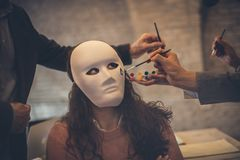 Why are you doing this to me. ? Business men paint a mask on a woman. Close up stock photos