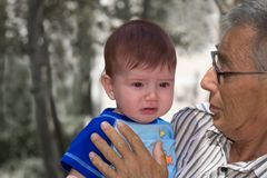 Why are you upset?. Crying baby with his gradpa Royalty Free Stock Photo