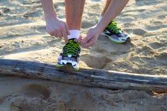 Wiąże jego buty na plaży Obraz Royalty Free
