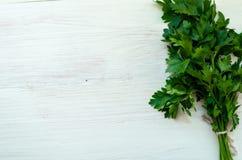 Wiązka świeża pietruszka na białych deskach Zdjęcie Royalty Free