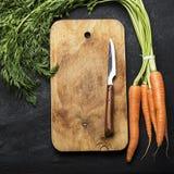 Wiązka świeże soczyste marchewki z wierzchołki na ciemnym tle z rocznik tnącą deską i nożu dla gotować Zdjęcia Royalty Free