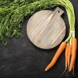 Wiązka świeże soczyste marchewki z wierzchołki na ciemnym tle z rocznik tnącą deską i nożu dla gotować Zdjęcia Stock