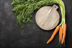 Wiązka świeże soczyste marchewki z wierzchołki na ciemnym tle z rocznik tnącą deską i nożu dla gotować Obraz Royalty Free