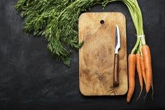 Wiązka świeże soczyste marchewki z wierzchołki na ciemnym tle z rocznik tnącą deską i nożu dla gotować Obraz Stock