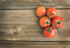 Wiązka świezi dojrzali czerwoni pomidory nad nieociosanym drewnianym tłem Obraz Stock