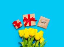 Wiązka żółci tulipany i piękni prezenty na cudownym błękicie Zdjęcia Royalty Free