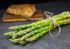 Wiązka asparagus z piec wieprzowiny tenderloin na drewnianej tnącej desce zdjęcie stock