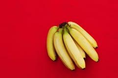 Wiązka banany na czerwonym tle Świeży organicznie banan, Świezi banany na kuchennym stole Fotografia Royalty Free