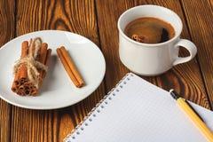 Wiązka cynamon dział z arkaną, filiżanka kawy i notatnikiem dla pisać na drewnianym tle w górę, fotografia stock