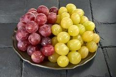 Wiązka czerwieni i zieleni winogrona na czarnym tło iłołupka kamieniu Zdjęcie Royalty Free