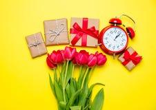 Wiązka czerwoni tulipany, budzik i piękni prezenty na wond, Zdjęcia Stock