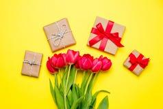 Wiązka czerwoni tulipany i piękni prezenty na cudownym kolorze żółtym Obraz Royalty Free