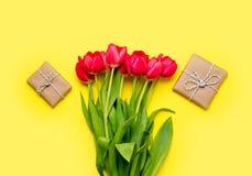 Wiązka czerwoni tulipany i piękni prezenty na cudownym kolorze żółtym Fotografia Stock