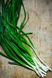 Wiązka długiej trzon zieleni świezi scallions na wietrzejącym drewnianym tle, odgórny widok, minimalista obrazy stock
