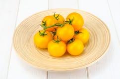 Wiązka dojrzali żółci pomidory na białym drewnianym stole obrazy stock