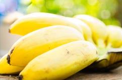 Wiązka dojrzali banany na drewnianej desce z plamy zieleni liścia backg Zdjęcia Royalty Free