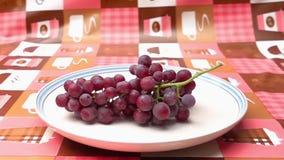 Wiązka dojrzali beznasienni winogrona spada w białego talerz zbiory