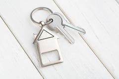 Wiązka klucze z domem kształtował keychain na białym drewnie Obrazy Royalty Free