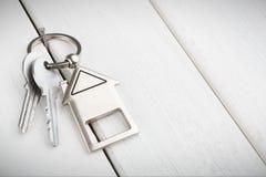 Wiązka klucze z domem kształtował keychain na białym drewnie Obraz Royalty Free